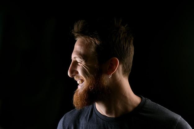 Portret van profiel van een glimlachende man op zwart
