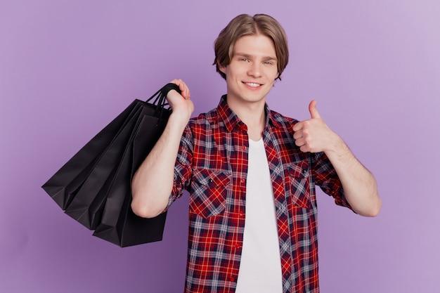 Portret van promotor-man steekt duim omhoog, houdt winkelpakketten vast met een brede glimlach op violette achtergrond