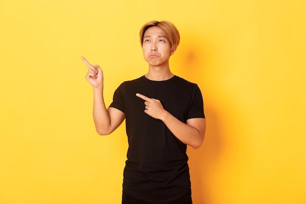 Portret van pruilende, boos en grappige aziatische kerel die en linkerbovenhoek met spijt richt, die gele muur kijkt.