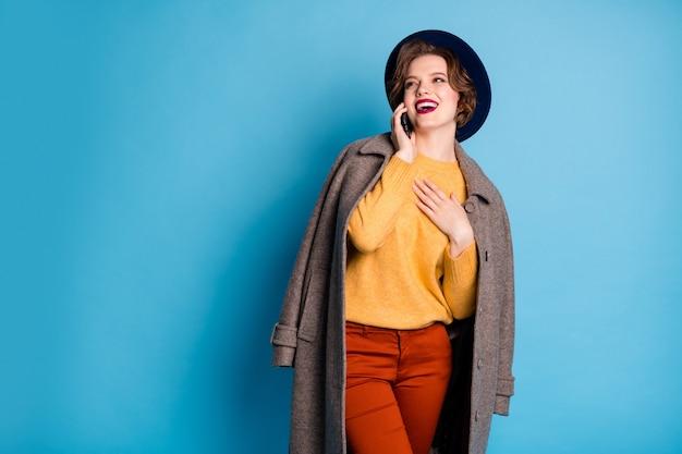 Portret van reiziger dame lopen straat spreken telefoon vrienden vragen weersvoorspelling dragen stijlvolle seizoen lange grijze jas pullover broek hoed outfit.