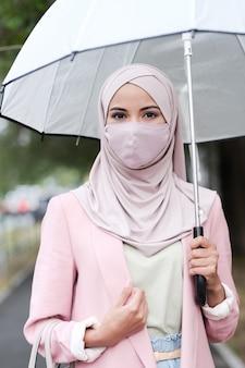 Portret van religieuze jonge vrouw in roze hijab en jas met paraplu op straat in de stad