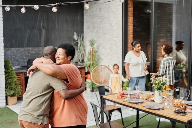 Portret van rijpe afro-amerikaanse vrouw die vriend omhelst tijdens familiebijeenkomst op etentje ou...