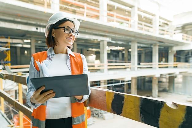 Portret van rijpe architectenvrouw bij bouwwerf