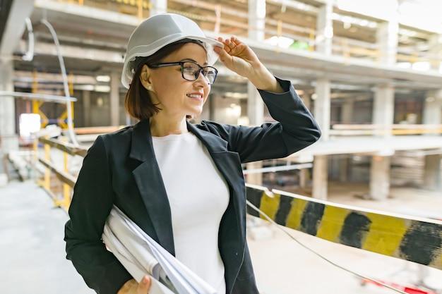 Portret van rijpe architectenvrouw bij een bouwwerf