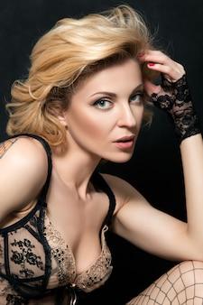 Portret van rijpe blonde sensuele vrouw in sexy linnen wat betreft haar haar