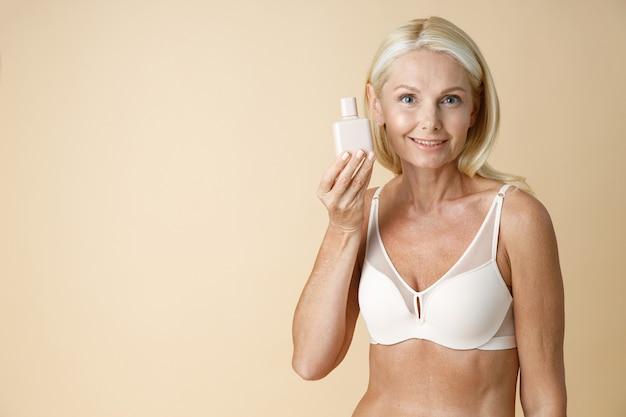 Portret van rijpe blonde vrouw in ondergoed met perfect lichaam glimlachend in de camera met wit