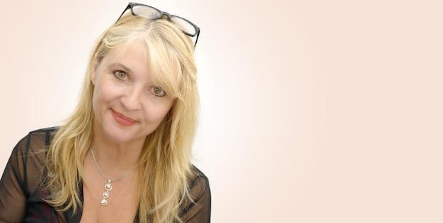 Portret van rijpe glimlachende blonde vrouw