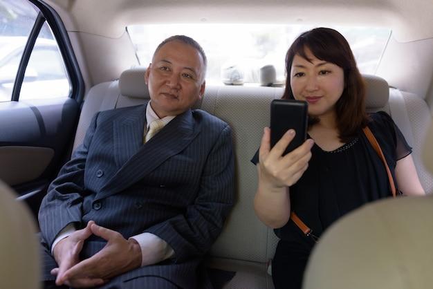 Portret van rijpe japanse zakenman en rijpe japanse vrouw die de stad bangkok verkennen