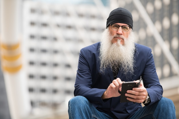 Portret van rijpe kale zakenman met lange baard die oogglazen in de stadsstraten buiten dragen