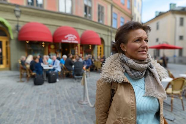 Portret van rijpe mooie scandinavische toeristenvrouw met kort haar die door de stad stockholm in zweden reizen