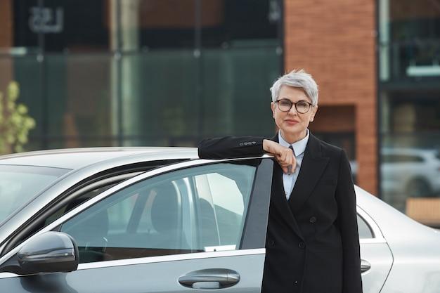 Portret van rijpe onderneemster in oogglazen die zich dichtbij de auto bevinden