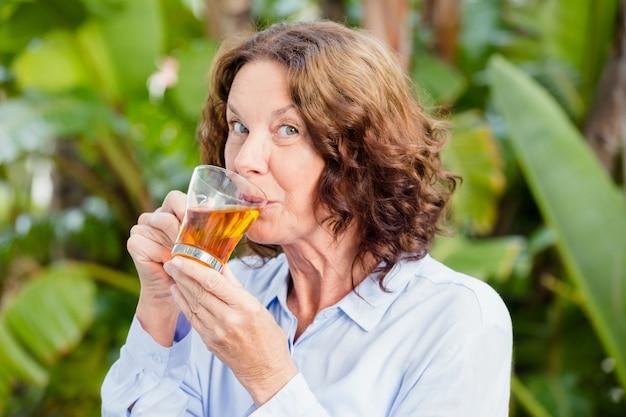 Portret van rijpe vrouw die aftreksel drinken