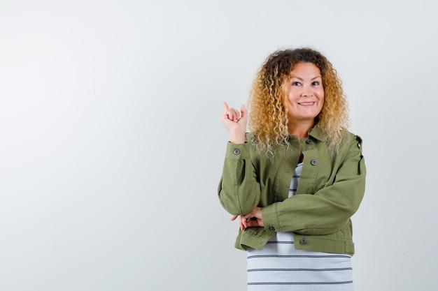 Portret van rijpe vrouw die terug wijst terwijl het glimlachen in groene jas, t-shirt en heel vooraanzicht kijkt