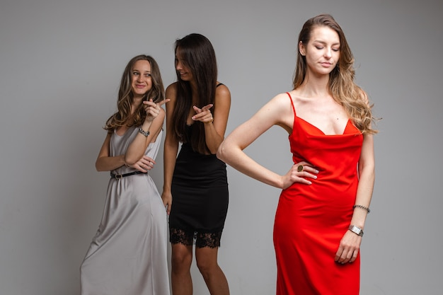 Portret van roddelende meisjes in zilveren en zwarte jurken spottend mooi ongelukkig meisje met lang blond haar in rode jurk staande op de voorgrond en droevig naar beneden kijken