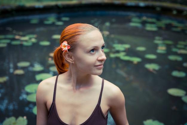 Portret van rode jonge vrouw met bloem