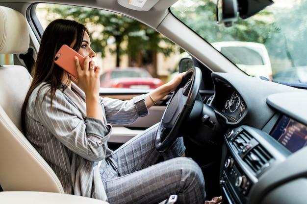 Portret van roekeloze bestuurder die haar mobiele telefoon spreekt tijdens het autorijden.