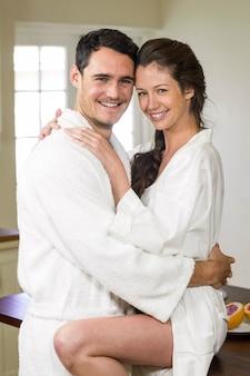 Portret van romantisch jong paar in badjas die elkaar in keuken knuffelen