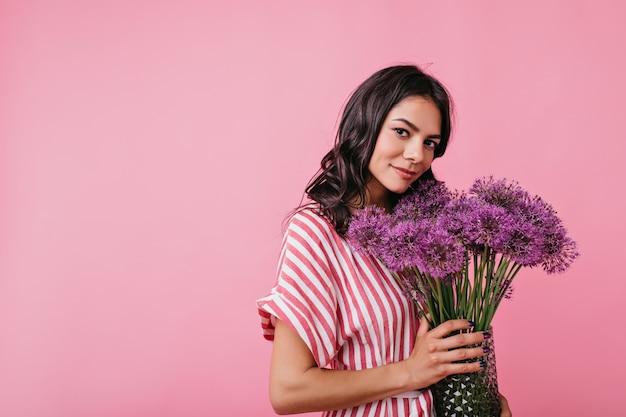 Portret van romantisch meisje met lila bloemen. brunette in roze jurk ziet er schattig uit.