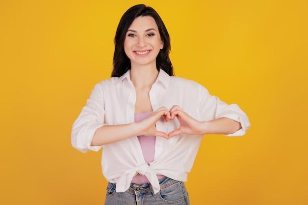Portret van romantisch meisje toont hartgebaar op gele achtergrond