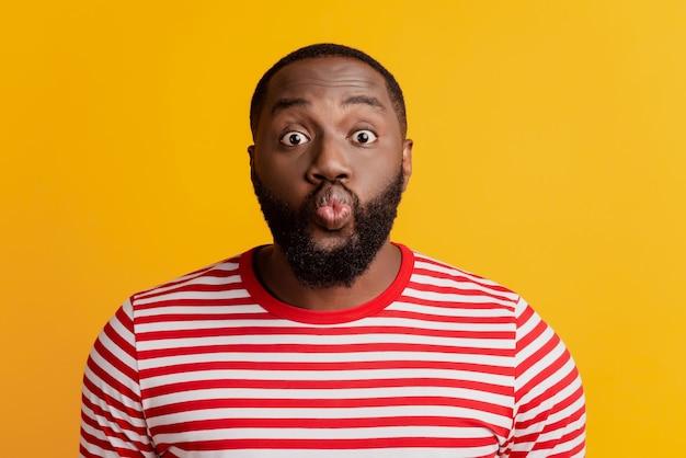 Portret van romantische aanhankelijke man blaast luchtkus op gele achtergrond