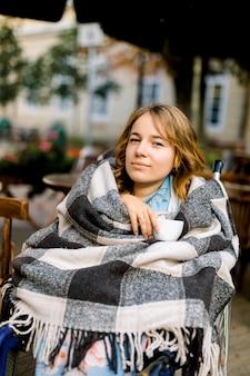 Portret van romantische blonde vrouw in een rolstoel, koffie drinken op café buiten in de stad