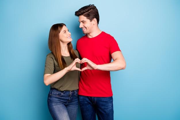 Portret van romantische cupido twee echtgenoten maken hartvorm handen leven lang liefde teken kijken dragen groene t-shirt denim jeans geïsoleerd op blauwe kleur achtergrond