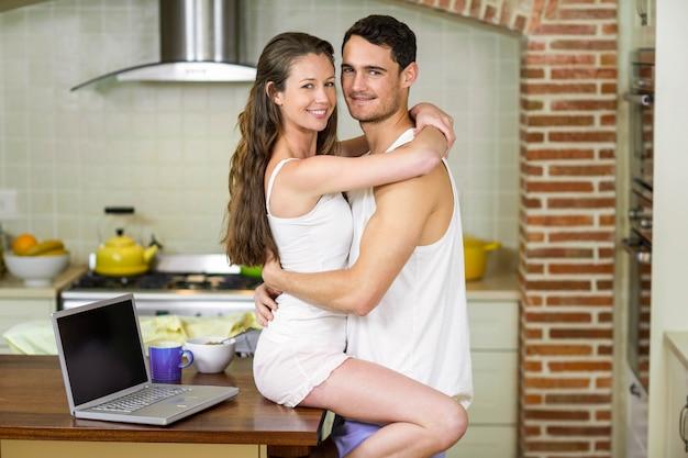 Portret van romantische jong koppel knuffelen op keuken aanrecht