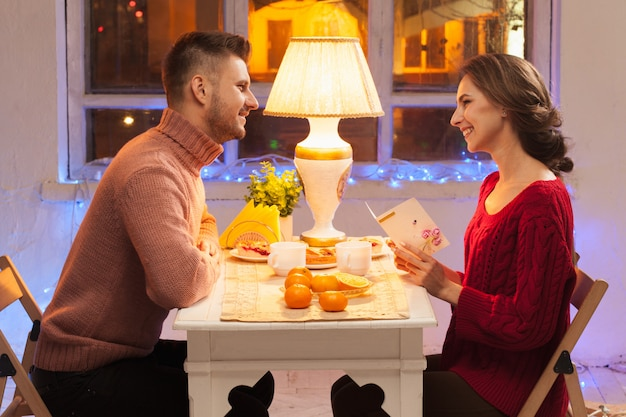 Portret van romantische paar bij valentijnsdag diner met cadeau