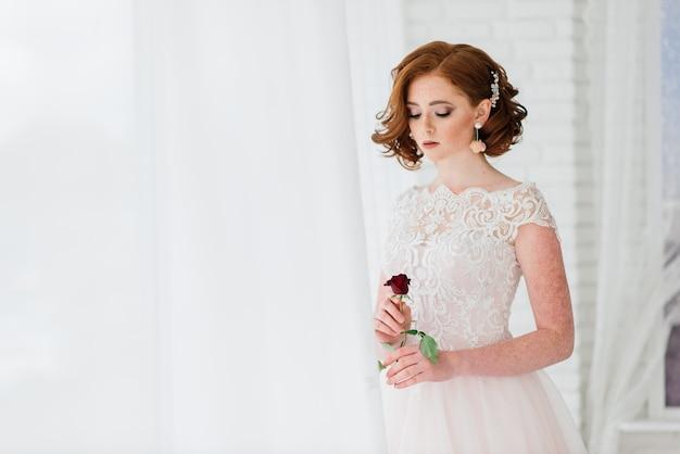 Portret van roodharig meisje dat trouwjurk draagt tegen een witte en grijze achtergrond.