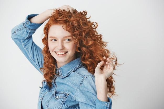 Portret van roodharige het mooie meisje glimlachen die in kant kijken. kopieer ruimte.