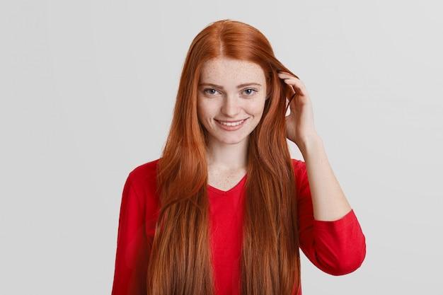 Portret van roodharige jonge vrouw met lang haar, heeft sproeten gezicht, aangename glimlach, raakt haar