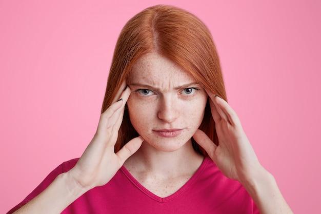 Portret van roodharige sproeterig vrouwtje probeert zich te concentreren, heeft een serieuze uitdrukking, houdt handen op de slapen, heeft hoofdpijn