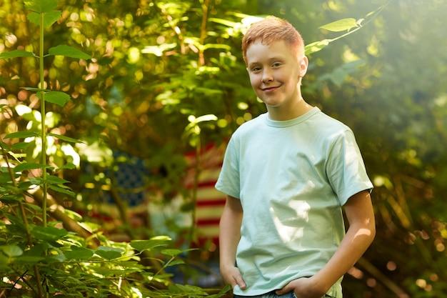 Portret van roodharige tiener die lacht terwijl hij buiten in bos of achtertuin staat