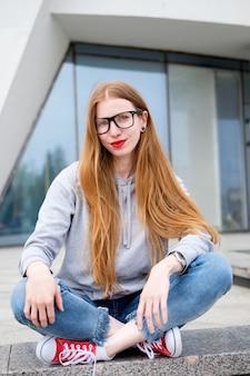 Portret van roodharige vrouw gekleed in hoody, jeans, rode sneakers en bril, met rode lippenstift geschilderde lippen op zoek recht in zonnige zomerdag