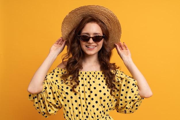 Portret van roodharige vrouw in strohoed en stijlvolle zonnebril poseren op geel in zomerjurk.