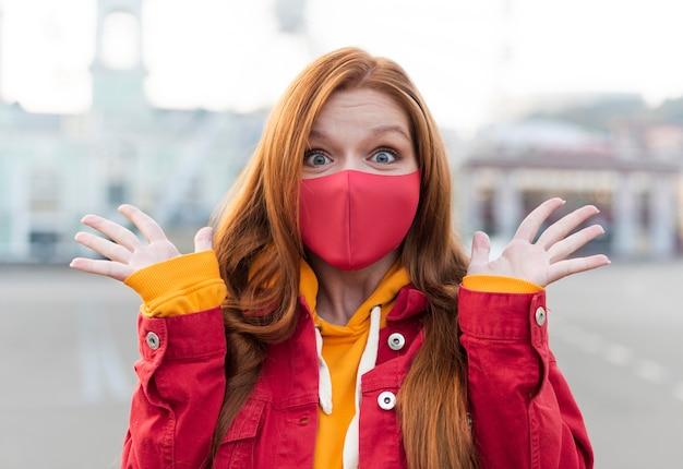Portret van roodharige vrouw met medisch masker