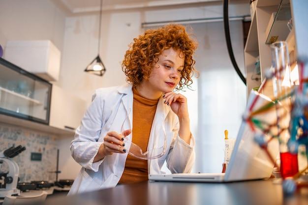 Portret van roodharige vrouwelijke wetenschapper in brillen die aan bureau zitten en met laptop werken tijdens wetenschappelijk experiment