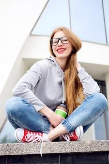 Portret van roodharigemeisje gekleed in hoody, jeans, rode tennisschoenen en glazen