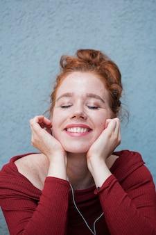 Portret van roodharigevrouw die aan muziek luisteren