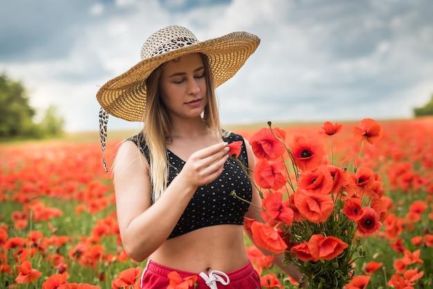Portret van rpetty oekraïense vrouw in zwarte top en hoed met groot boeket van papavers in veld. zomertijd