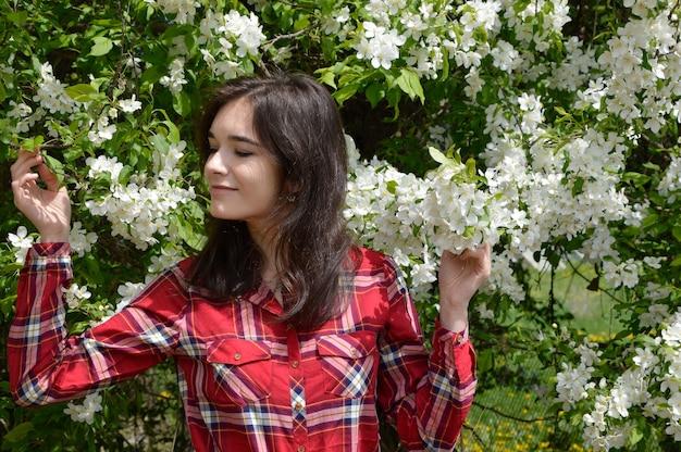 Portret van russische brunette vrouw aanraken en ruiken bloeiende takken van de boom