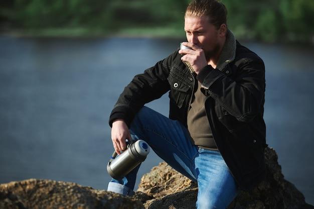 Portret van rustende bergbeklimmer en het drinken van hete thee of koffie bij meer. concept van ontspanning en reizen in de natuur