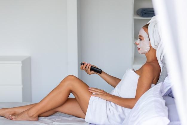 Portret van rustige blanke mooie vrouw met een handdoek op het hoofd en oogmasker patches op het gezicht gezicht huid zorg concept vrouw ontspannen op bed thuis