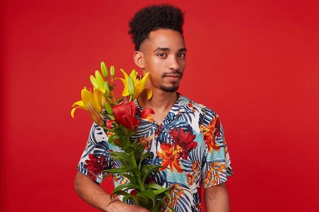 Portret van rustige jonge afro-amerikaanse man, draagt in hawaiiaans shirt, kijkt naar de camera, houdt gele en rode bloemen, staat op rode achtergrond.