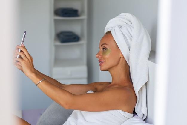 Portret van rustige kaukasische mooie vrouw met een handdoek op het hoofd en oogmasker patches op gezicht gezicht huid zorg concept vrouw ontspannen op bed thuis selfie horloge telefoon nemen