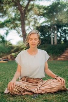 Portret van rustige mooie jonge vrouw die mediteert