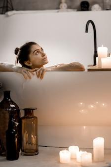 Portret van rustige vrouw met vrije tijd in water met schuim tegenover kaarsen in appartement, gezonde behandeling en plezier.