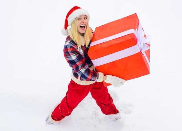Portret van santa vrouw met enorme rode gift camera kijken - volledige lengte. verpakt kerstcadeau