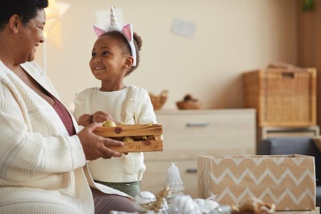 Portret van schattig afrikaans-amerikaans meisje huis versieren voor kerstmis met liefdevolle oma terwijl u geniet van vakantieseizoen thuis, kopieer ruimte
