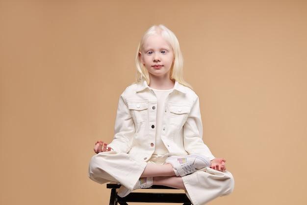 Portret van schattig albino kind model mediteren in lotus houding